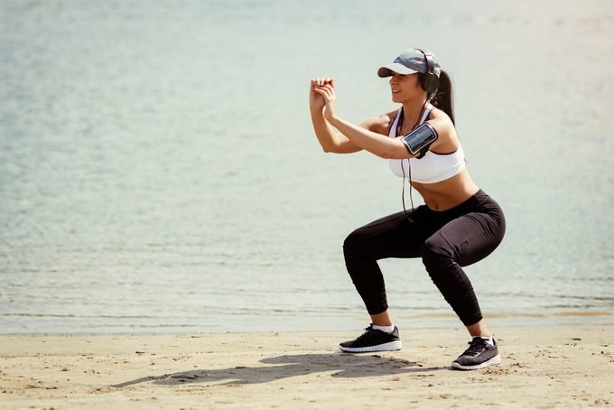 Young muscular fitness woman doing squats exercise by the river.