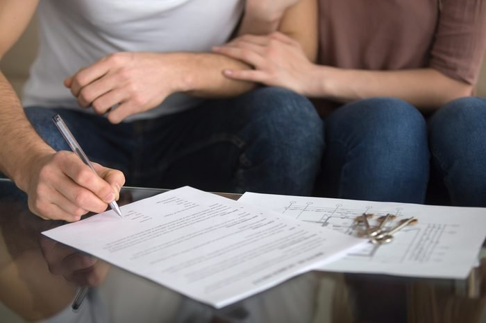 Buying and renting new home concept. Close up of loving couple signing rental agreement or sale purchase contract sitting on couch indoors, starting family life, approved loan to buy real estate