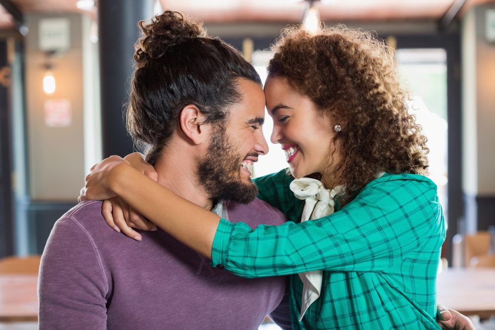 Cheerful young couple embracing in restaurant