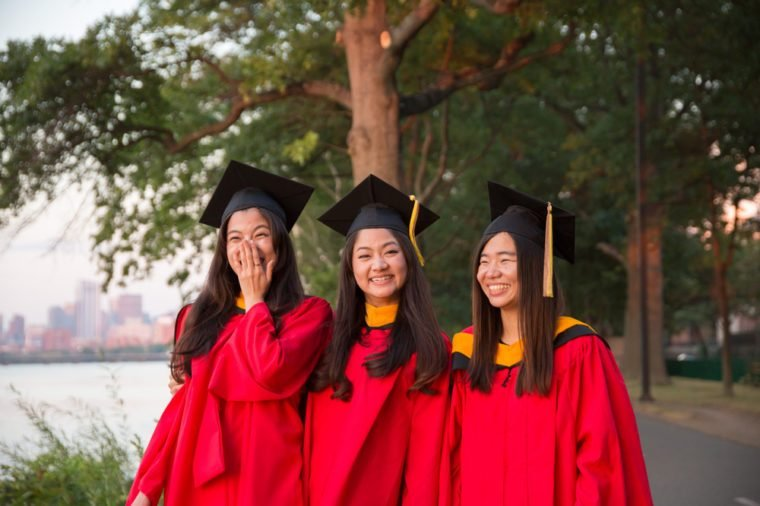 Group of Asian Female Graduates in Red Graduation Gowns Standing by Charles River at Sunset