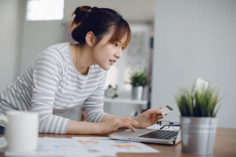 Young Asia woman holding credit card and using laptop computer.Online shopping concept