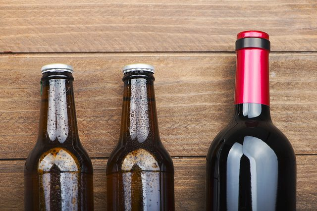 Top view of two beer bottles and a wine on wooden table