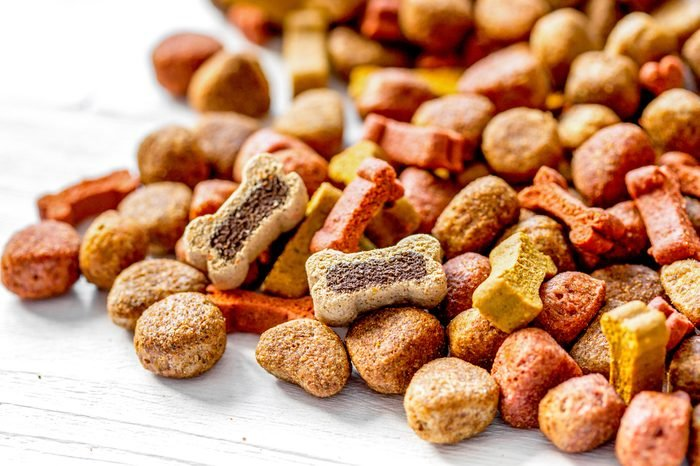 dry dog food in bulk on wooden background close up