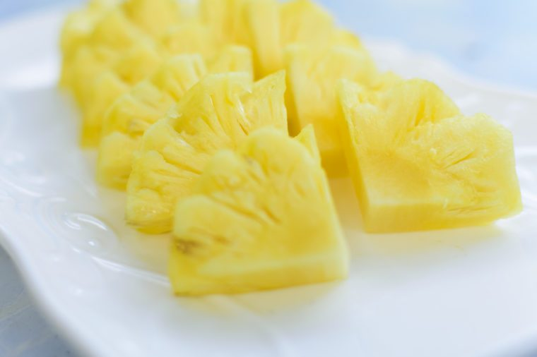 White plate pineapple on blue background.Close up.