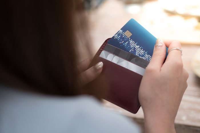 women is selecting credit card from her card wallet