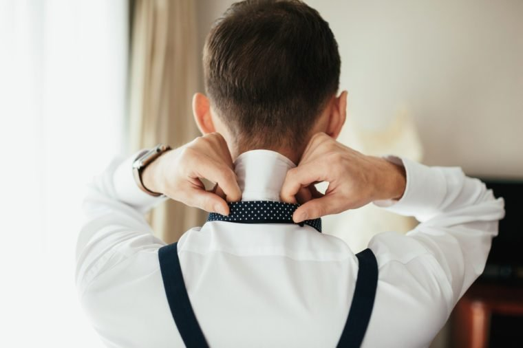 Man puts on a bow tie