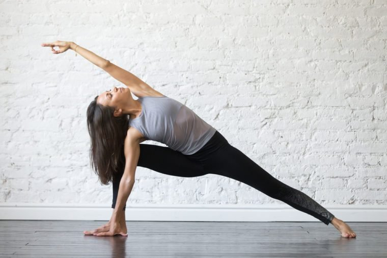 Young woman practicing yoga, stretching in Utthita parsvakonasana exercise, Extended Side Angle pose, working out, wearing sportswear, gray tank top, black pants, indoor full length, studio background
