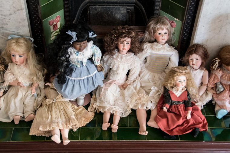 Antique porcelain doll collection laid out in front of old fireplace