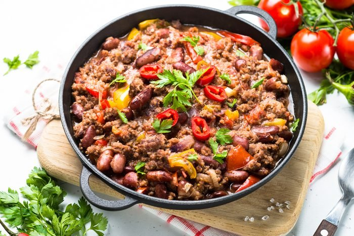 Chili con carne in a cast iron pan on white. Traditional mexican food.