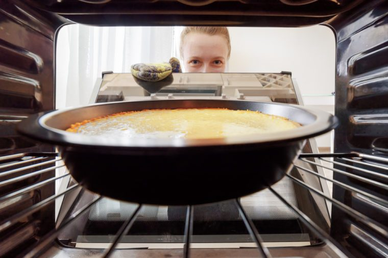 Young housewife looking at cheesecake into oven in kitchen. View from inside of the oven. Woman holding the oven door.