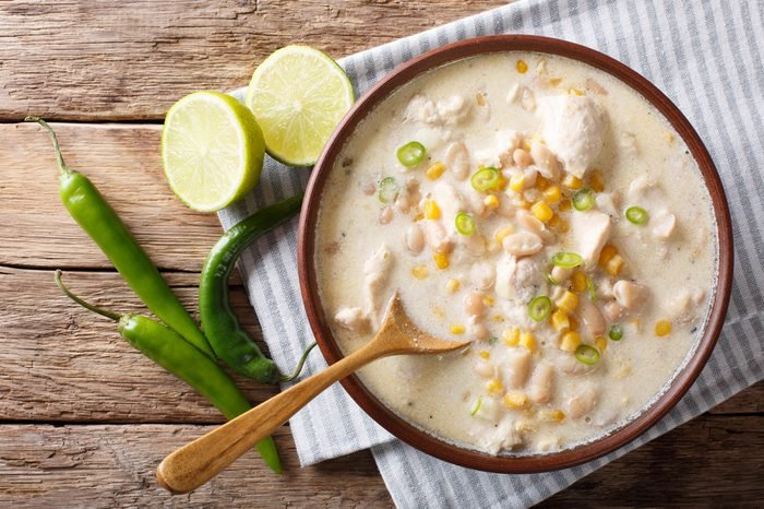 White chili chicken with beans, corn and spices close-up in a bowl. horizontal top view from above