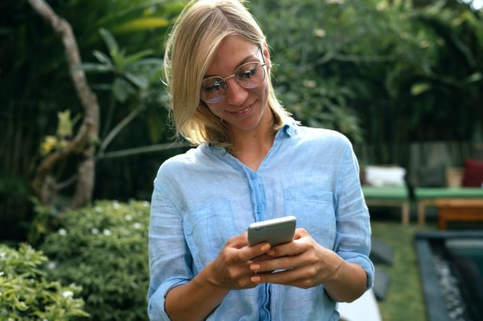 Model look female wearing glasses is reading emails on her mobile phone while relaxing on a luxury tropical villa. Travel blogger wearing light blue shirt is surfing the web on a smartphone.