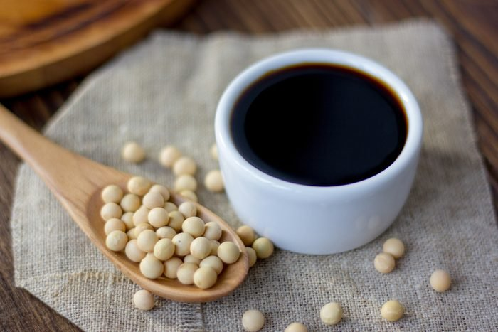 White ceramic bowl with soy sauce on kitchen.