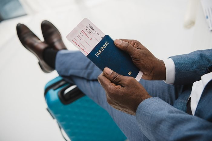 Cropped image of African american man holding passport and fly ticket in hands