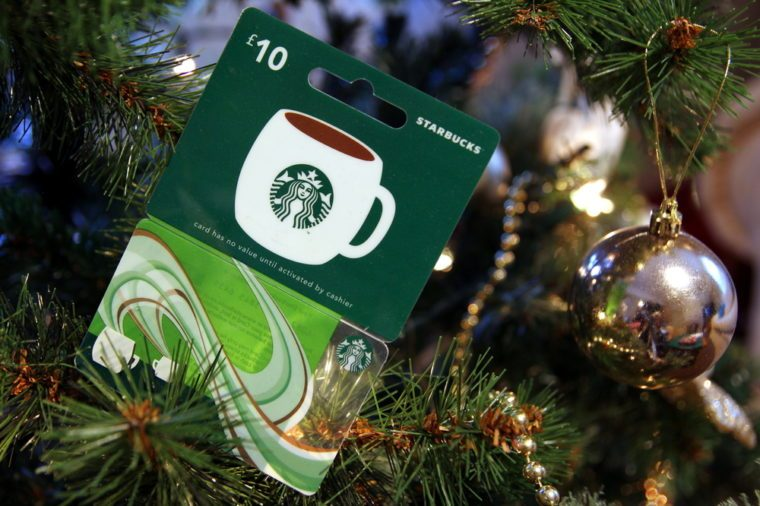 British Starbucks £10 gift card or voucher, nestled among the branches of a Christmas tree
