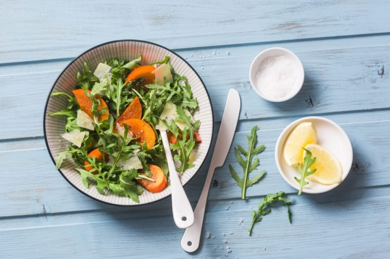 Parmesan cheese, persimmons, arugula salad. Healthy vegetarian food, snack. Seasonal, comfort food. On a blue background, top view