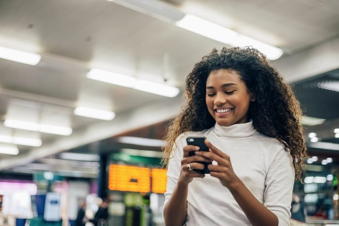 Woman check flight number on mobile phone in airport.