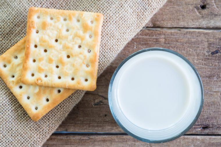 stack of crackers on gunny sack cloth on wooden table with a cup of milk, top view, close up