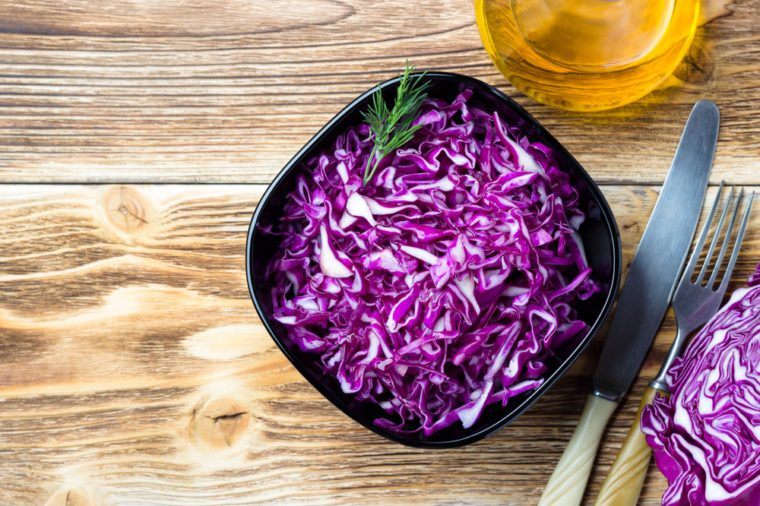 Red cabbage salad on wooden background. Top view.