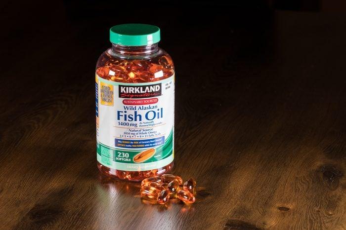 Kirkland Wild Alaskan Fish Oil capsules and bottle on wooden table