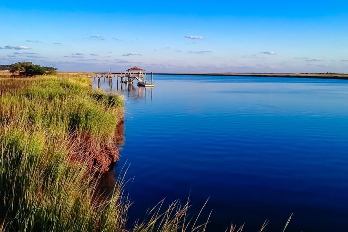 Dock on Daufuskie Island in Beaufort, South Carolina surrounded by marsh and deep blue waters from the intercoastal waterway.