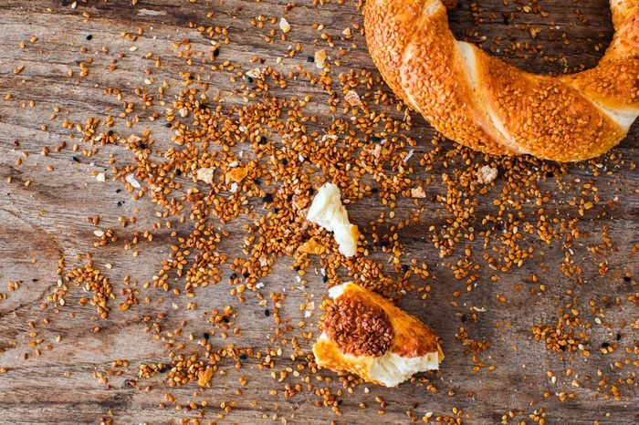 Turkish bagel simit pieces and sesame seeds crumb on wooden background