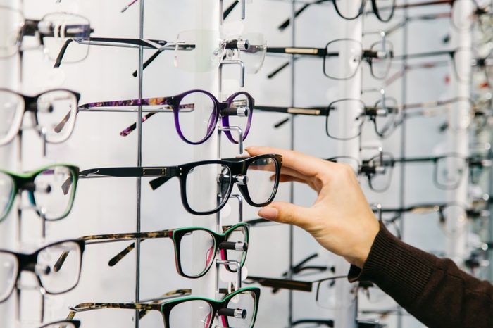 Eyeglasses shop. Stand with glasses in the store of optics. Woman's hand chooses glasses.