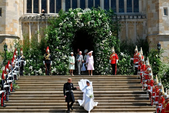 Prince Harry and Meghan Markle stand on the steps