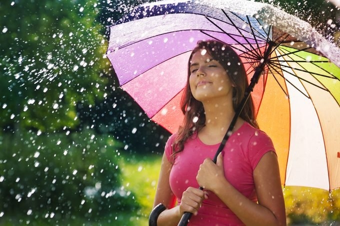 Young woman breathing fresh air during the spring rain
