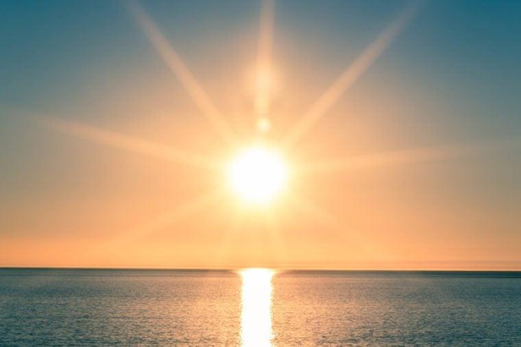 Sunset over Ocean - Bright Orange Sun Setting on Beautiful Blue Water
