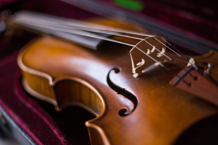 Violin and bow in dark red case. Close up