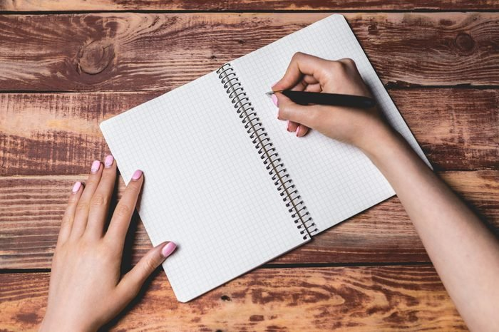 student writing in the notebook with black pen on wooden surface