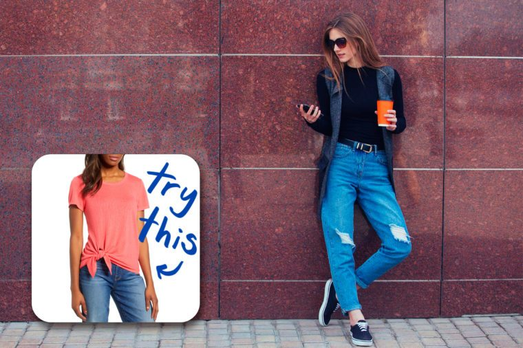 fashionable woman standing against wall holding phone and coffee cup. try this clearance tee.