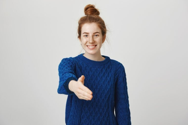 Happy to finally meet you. Studio shot of confident relaxed and friendly young woman with red hair combed in bun pulling head towards camera for handshake with cute smile, standing over gray wall