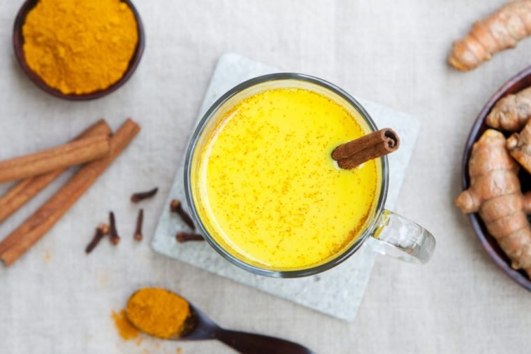 Turmeric drink, latte, tea, milk with cinnamon in a glass mug with fresh and dried turmeric on a textile grey background. Top view. Copy space.