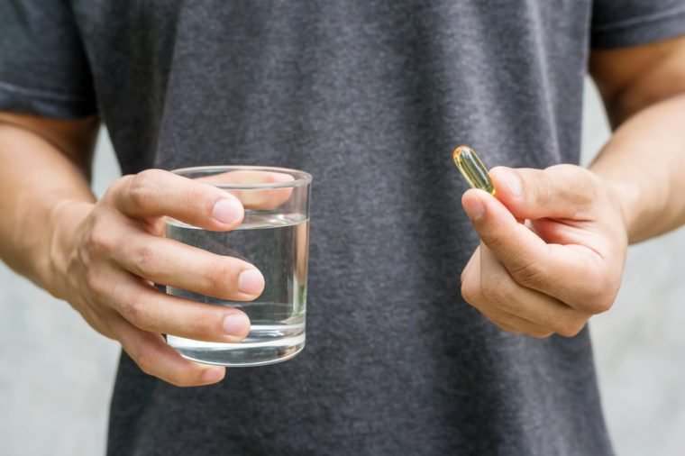Close up of a man holding a fish oil capsule and a glass of water.