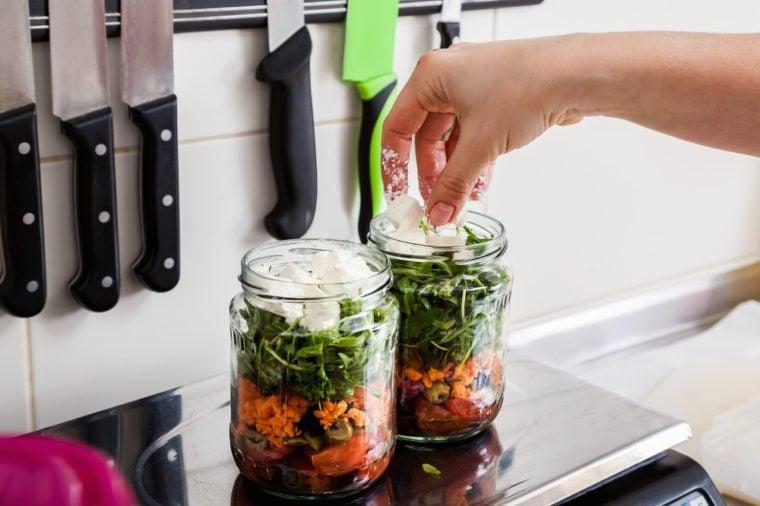 Making Jar Salads. Close Up Of Human Hand Putting Ingredients In Jar