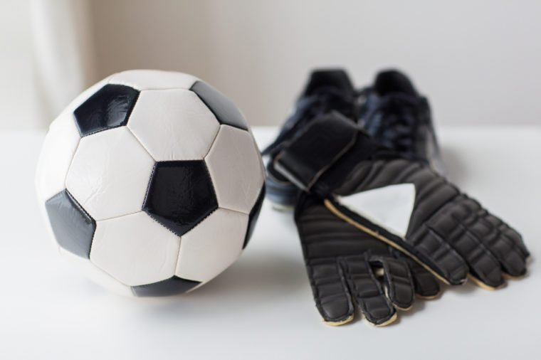 sport, soccer, football and sports equipment concept - close up of ball, boots and goalkeeper gloves on table