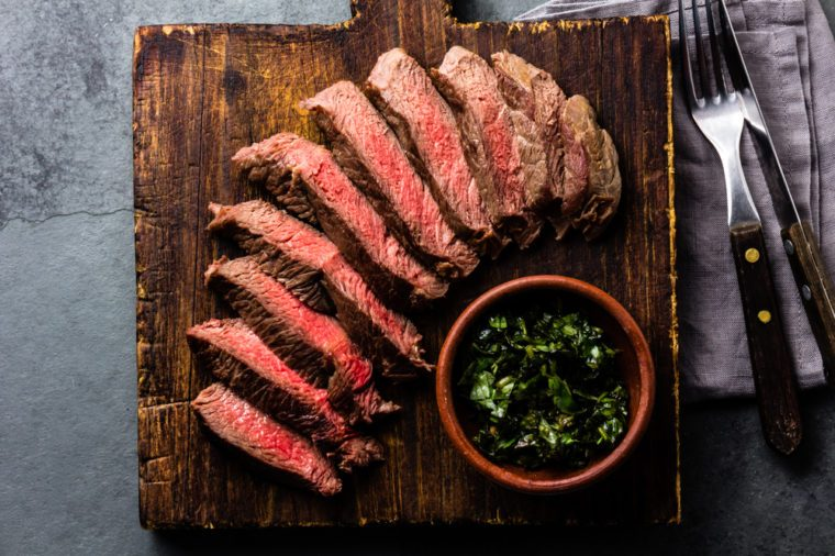 Medium rare sliced beef served on wooden board. Sliced medium rare roast beef on slate gray background