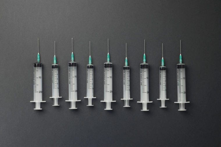 Syringes organized in a row over dark grey background, top view