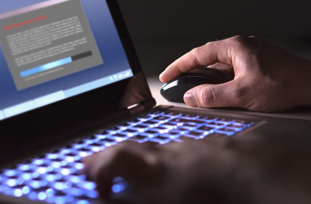 Man installing software in laptop in dark at night. Hacker loading illegal program or guy downloading files. Cyber security, piracy or virus concept.