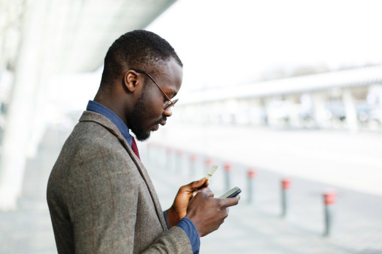 Stylish African American black businessman types information from his credit card to the smartphone standing before a modern glass building outside