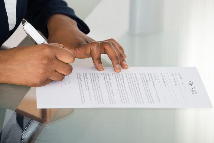 Close-up Of A Person's Hand Signing Contract