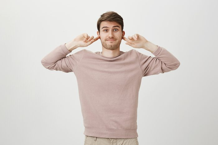 Indoor portrait of confused smiling caucasian man covering ears with forefingers, standing with awkward expression over gray background. Guy do not want to listen about his friend love affairs