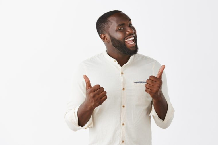 Indor shot of funny and emotive joyful dark-skinned guy with beard in trendy outfit, showing thumbs up and turning face at camera, smiling broadly, liking great and awesome party over gray background