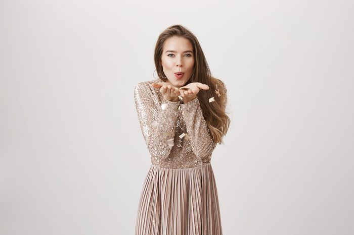 Studio portrait of beautiful feminine caucasian girl blowing confetti from hands, looking playfully and excited at camera, standing in elegant evening dress over gray background.