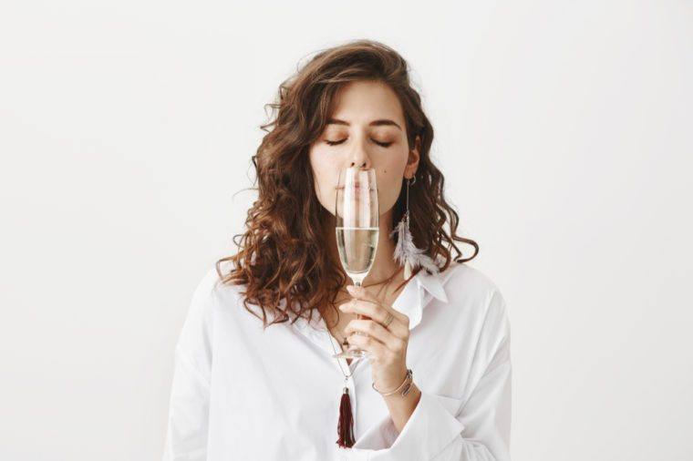 Studio portrait of beautiful sensual caucasian brunette smelling white wine while holding glass near nose, standing with closed eyes and enjoying taste over gray background.