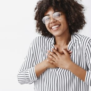Close-up shot of touched and pleased happy dark-skinned girl with afro hairstyle in glasses and striped blouse holding hands on chest and smiling broadly being pleased receiving compliments