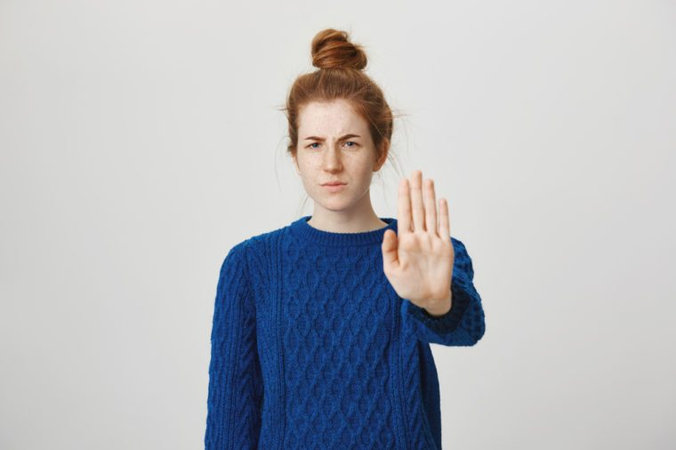 I am not interested live me alone. Portrait of annoyed angry good-looking redhead female in winter sweater pulling palm at camera with stop or no gesture, displeased while standing over gray wall