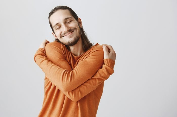 Who need girlfriends if you can hug yourself. Funny playful european guy with long hair and beard cuddling himself and smiling from pleasure, closing eyes and dreaming about finding soulmate